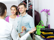 Female assistant serving happy customers. Female assistant serving beautiful customers asking in clothing boutique Stock Image