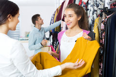 Female assistant serving happy customers. Beautiful female assistant serving customer asking in clothing boutique Stock Photo