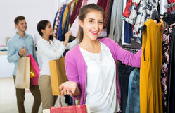 Female assistant serving happy customers. Beautiful female shopper chooses liked things in the boutique Royalty Free Stock Photography