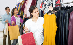 Female assistant serving happy customers. Beautiful young women customers chooses liked things in the boutique Royalty Free Stock Photo