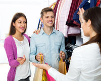 Female assistant serving happy customers Royalty Free Stock Photos