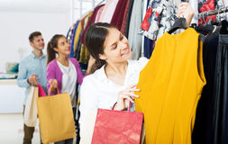 Female assistant serving happy customers. Cheerful young female shopper chooses liked things in the boutique Stock Photography