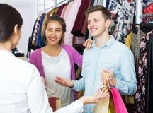 Female assistant serving happy customers. Female assistant serving happy couple customers asking in clothing boutique Royalty Free Stock Image