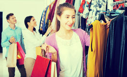 Female assistant serving happy customers. Positive female shopper chooses liked things in the boutique Stock Photography