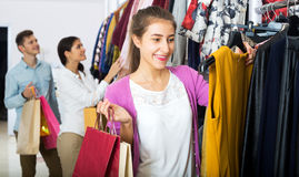 Female assistant serving happy customers. Positive female shopper chooses liked things in the boutique Royalty Free Stock Photos