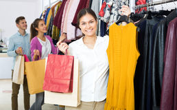 Female assistant serving happy customers. Positive young women customers chooses liked things in the boutique Stock Photos