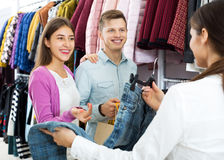 Female assistant serving happy customers. Female assistant serving smiling customers asking in clothing boutique Stock Photos