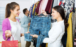 Female assistant serving happy customers. Smiling female assistant serving customer asking in clothing boutique Royalty Free Stock Photography