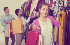 Female assistant serving happy customers. Smiling female shopper chooses liked things in the boutique Royalty Free Stock Photos