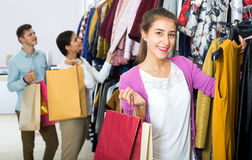 Female assistant serving happy customers. Smiling female shopper chooses liked things in the boutique Royalty Free Stock Photo