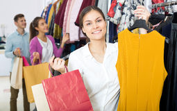 Female assistant serving happy customers. Smiling young female shopper chooses liked things in the boutique Stock Images