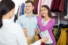 Female assistant serving happy customers. Female assistant serving young customers asking in clothing boutique Royalty Free Stock Images