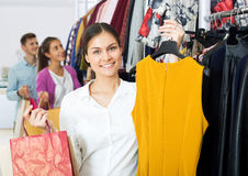 Female assistant serving happy customers. Happy young women customers chooses liked things in the boutique Royalty Free Stock Image