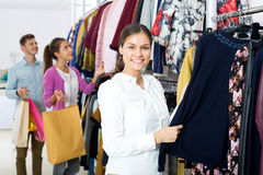 Female assistant serving happy customers. Young women customers chooses liked things in the boutique Royalty Free Stock Images
