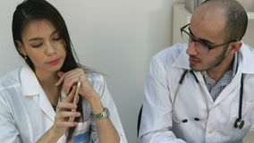 Female assistant talking on the phone asking male doctor for advice stock footage