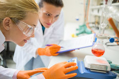 Female assistants adjust device for measuring liquid. Two female assistants adjust device for measuring liquid in chemical lab royalty free stock photos