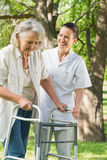 Female assisting mature woman with walker at park Royalty Free Stock Photos