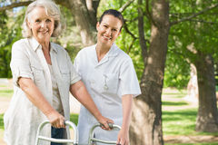 Female assisting mature woman with walker at park Stock Photos