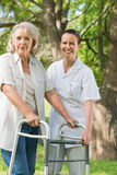 Female assisting mature woman with walker at park. Smiling young female assisting mature women with walker at the park Stock Photography