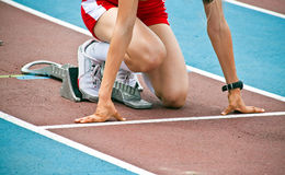 Female athlet in a starting block. On an athletic track stock images