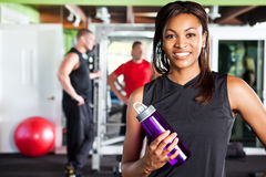 Female athlete. A shot of a happy black female athlete holding a water bottle in a gym Royalty Free Stock Image