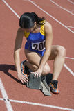Female Athlete Adjusting Starting Block Stock Photography
