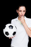 Female athlete blowing a whistle and holding a soccer ball. On black background stock photo
