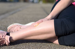 Female athlete with calf cramps. Lying on the sidewalk of a tarred road clutching her lower leg muscles in agony Stock Photo