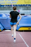 Female athlete competing in the pole vau. A female athlete competing in the pole vault at a track and field event Stock Photos