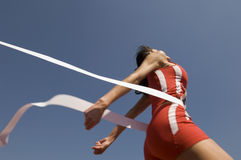 Female Athlete Crossing Finish Line Against Blue Sky. Low angle view of young female athlete crossing finish line against clear blue sky Stock Photo