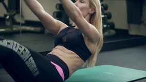 Female athlete doing abdominal crunches lying on floor in gym. stock footage