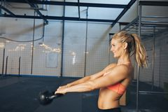 Female athlete doing crossfit workout. Side view of happy young  woman exercising with kettle bell at gym. Caucasian female athlete doing crossfit workout at gym Royalty Free Stock Images