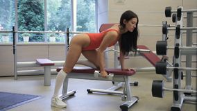 Female athlete is doing dumbbell row exercise in gym indoors. Woman leans with one hand and leg on bench, with exhalation lifts dumbbell, bending elbow and stock video
