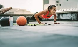 Female athlete doing fitness workout on rooftop. Woman athlete doing push ups on the rooftop with medicine ball and basketball by her side. Woman in fitness wear royalty free stock photo