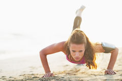 Female athlete doing push ups on beach Royalty Free Stock Photo
