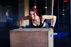 Female athlete doing push ups on wooden box Royalty Free Stock Photos