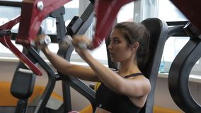 Female athlete doing seated front press on machine in gym indoors. stock video