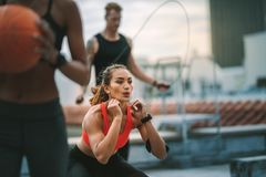 Fitness man and women training on rooftop. Female athlete doing squats on rooftop with her colleagues training with basketball and skipping rope. Fitness people royalty free stock image