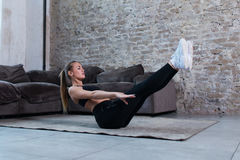 Female athlete doing static abs v hold exercise strengthening core muscles on floor in loft studio.  Royalty Free Stock Image