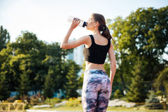 Female athlete drinking from water bottle after workout at stadium Royalty Free Stock Photo