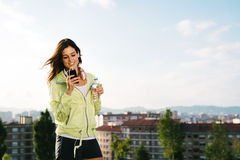Female athlete  drinking water and messaging on smartphone. Female athlete messaging with smartphone while holding bottle of water. Fitness woman looking her Royalty Free Stock Photos