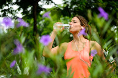 Female athlete drinking water during running rest Stock Images