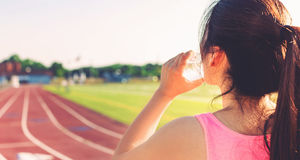Female athlete drinking water on a running track Royalty Free Stock Images