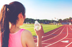 Female athlete drinking water on a running track Royalty Free Stock Photo