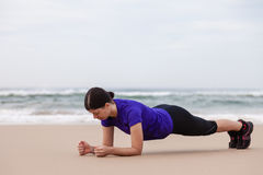 Female athlete executing the plank exercise. At the beach on an Autumn day royalty free stock image