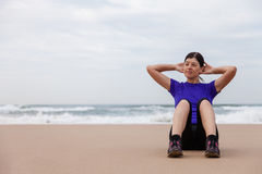 Female athlete executing situps at the beach Royalty Free Stock Image