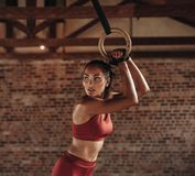Female athlete exercising with gymnastic rings Stock Photo