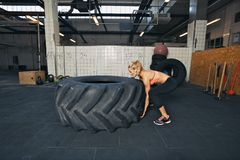 Female athlete flipping a tire while working out Royalty Free Stock Photos