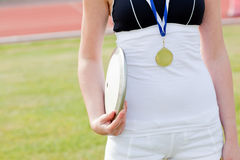 Female athlete with a gold medal holding a discus Royalty Free Stock Photos