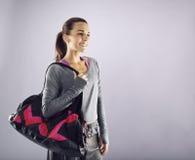 Female athlete with gym bag looking away smiling. Image of beautiful caucasian female athlete with gym bag looking away smiling. Young woman in sportswear Stock Image